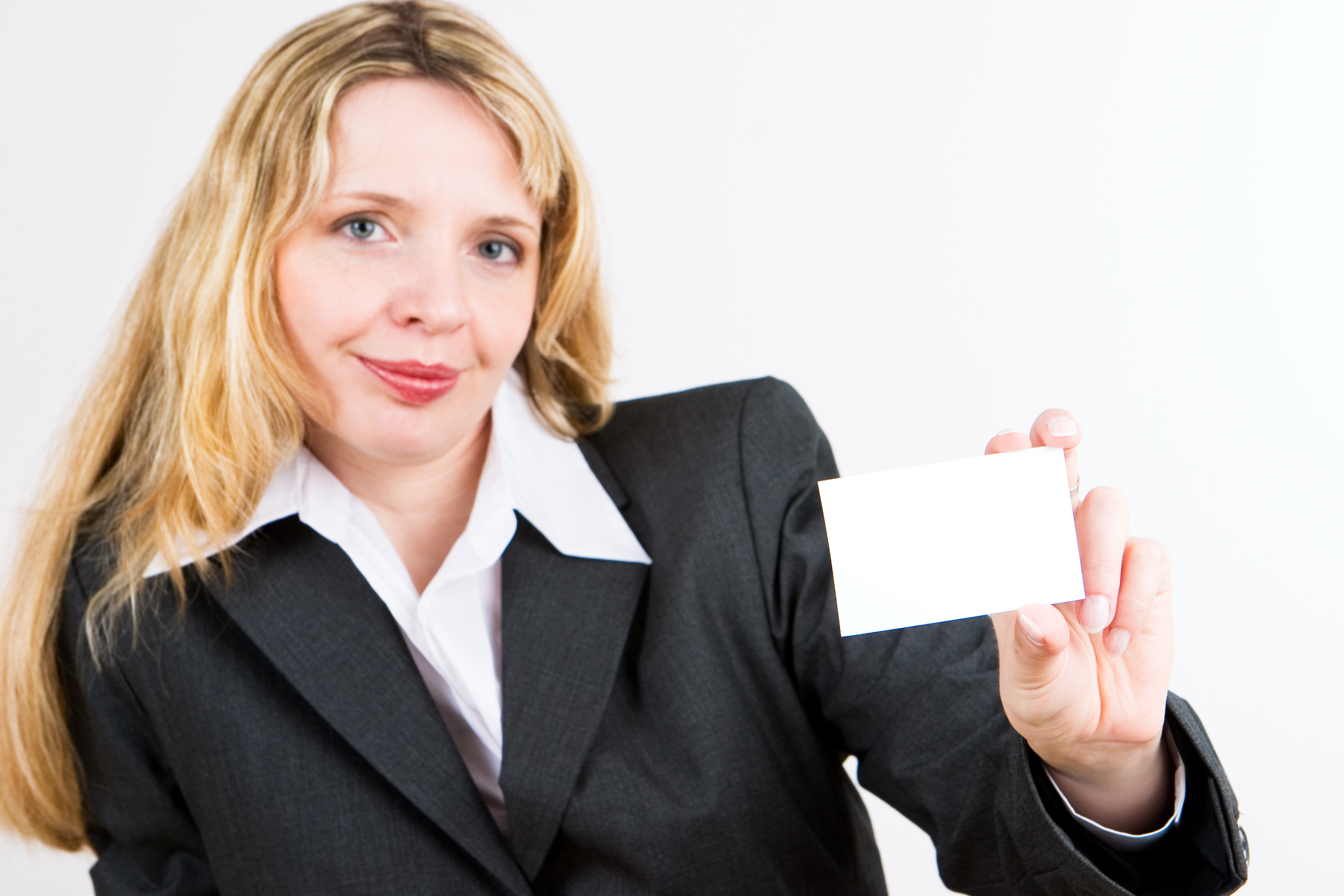 A blond business woman in a suit holding a blank business card