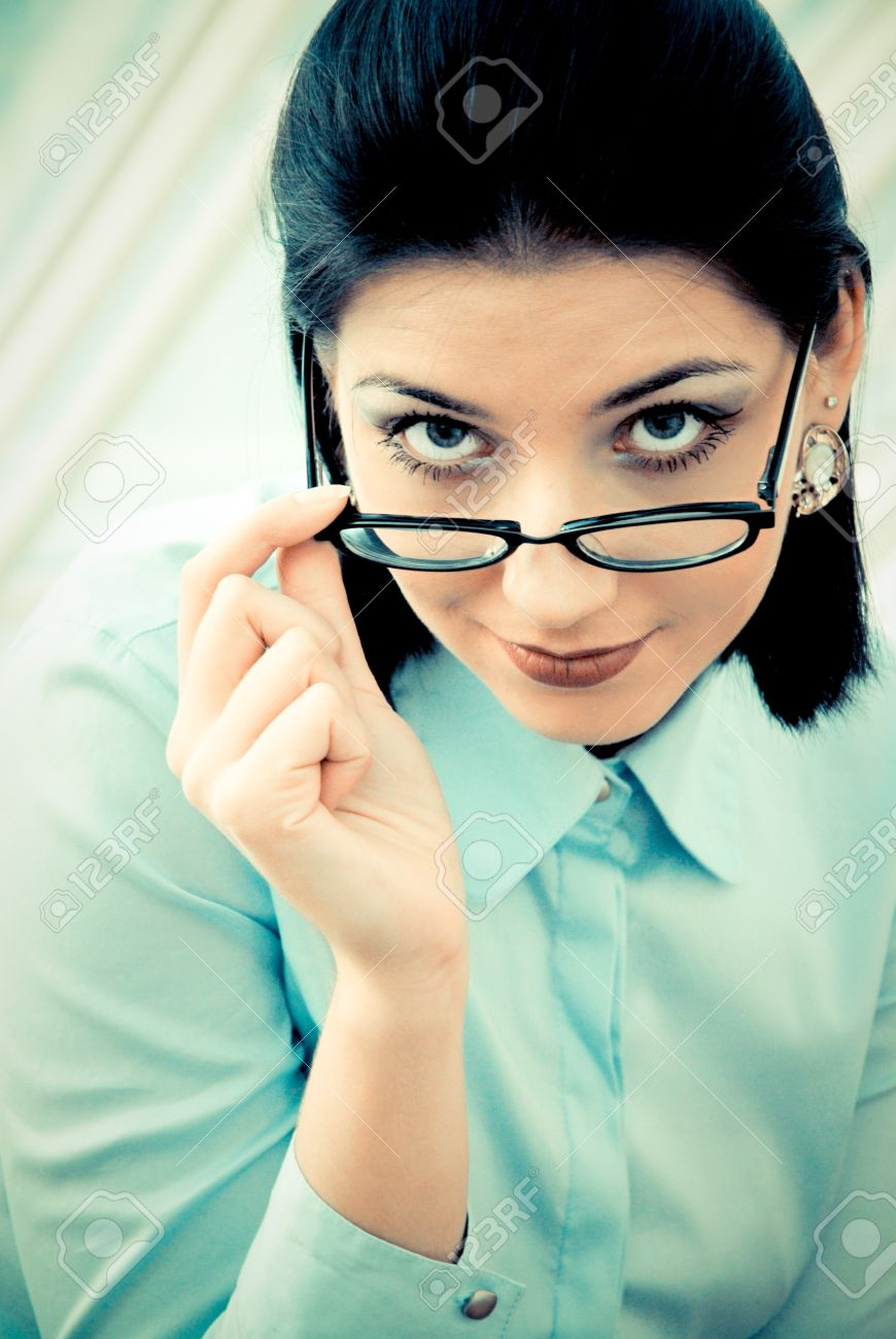 13785493-Serious-business-woman-looking-over-spectacles-Stock-Photo[1]